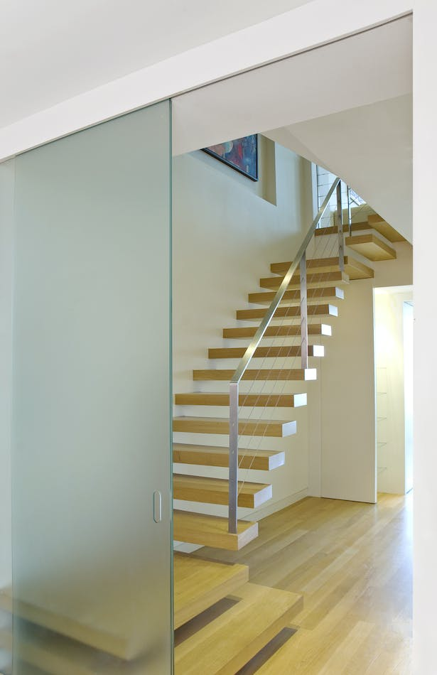 The cantilevered stair is the centerpiece of this apartment combination and renovation. The floating oak treads match the oak floors but contrast with the exquisite stainless steel cable railing. The visual simplicity of the stair belies the complexity of the structural and detail coordination needed to achieve this degree of minimalism.