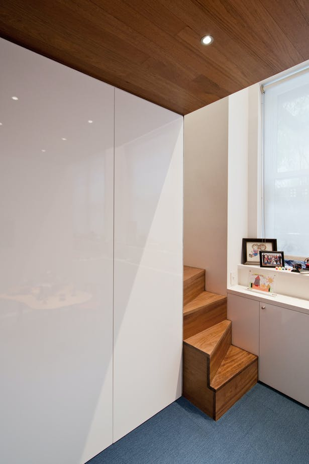 Glossy White Full Height Cabinets Provide Storage and a Counterbalance to the Rich Woods