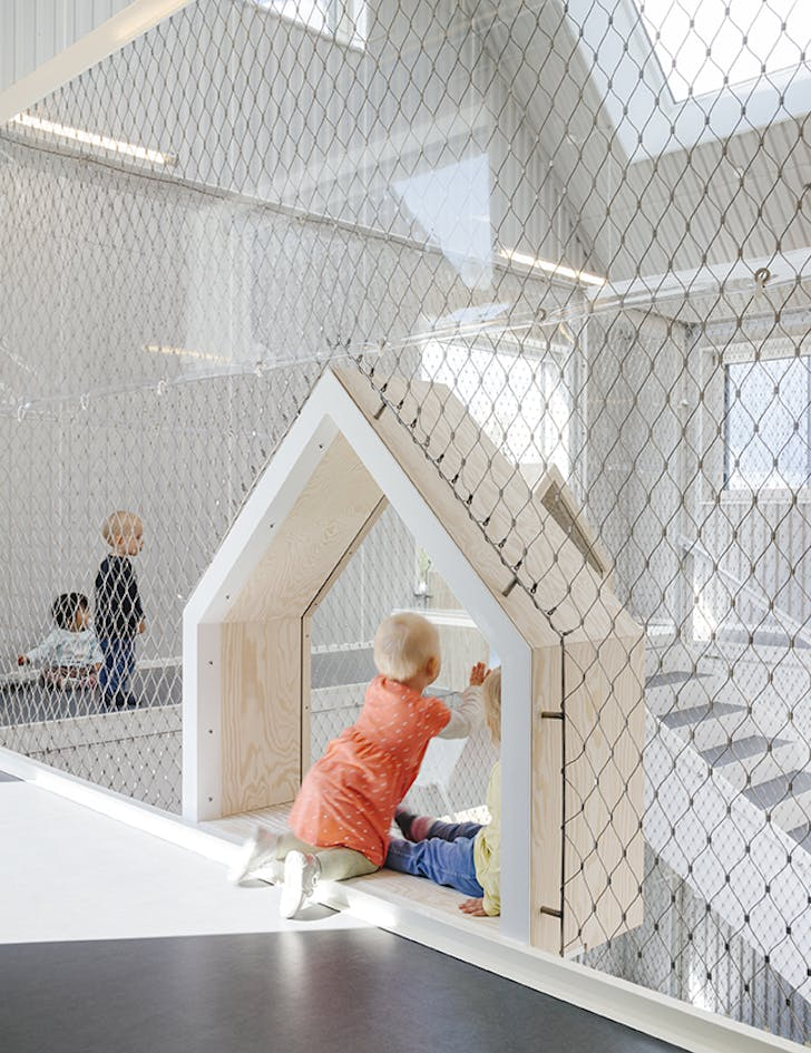 The interior of the kindergarten is bright and clutter-free. Plexiglas ensures that the children may safely play along the atrium's balconies.