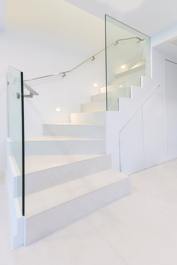 A stainless steel flat-bar handrail was installed directly onto the glass panel, which then transitions to becoming wall mounted.