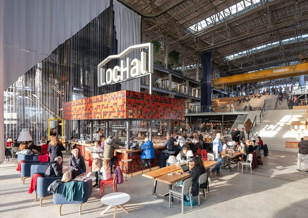 The eye-catcher is the city café featuring a bar with red, brown and gold ceramic tiles and a neon LocHal logo on top. It can easily be spotted from passing trains.