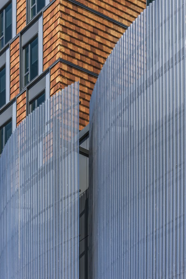 The exterior of the residential tower is clad in a vertical terracotta tile rainscreen, its variegated tones lightening as the height of the building increases. A curved screen made of perforated corrugated stainless steel panels adds contrast and a veil-like elegance to the façade of the performance wing. Photo credit: Peter Vanderwarker