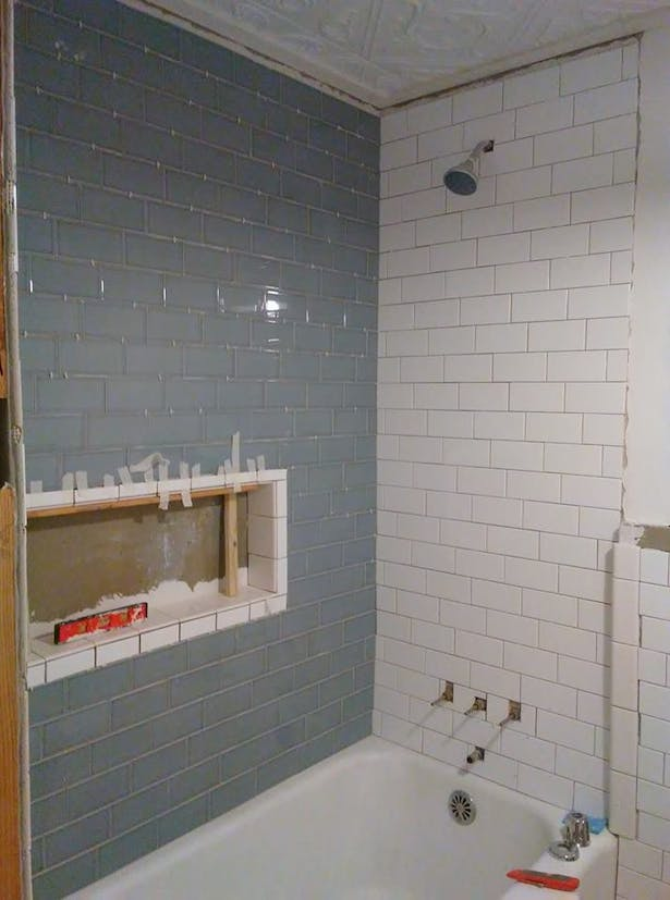 New wall sheathing & subway tile installed around the existing cast iron tub.