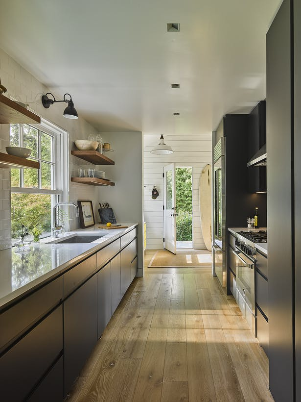 A sleek kitchen with natural wood floors and shelves.