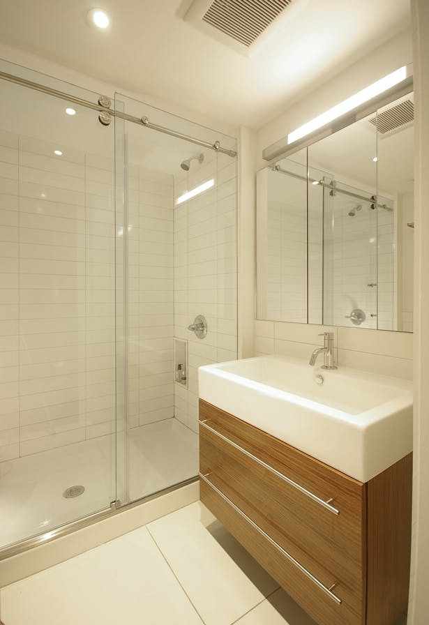 Contemporary materials and minimal details extend to bathrooms