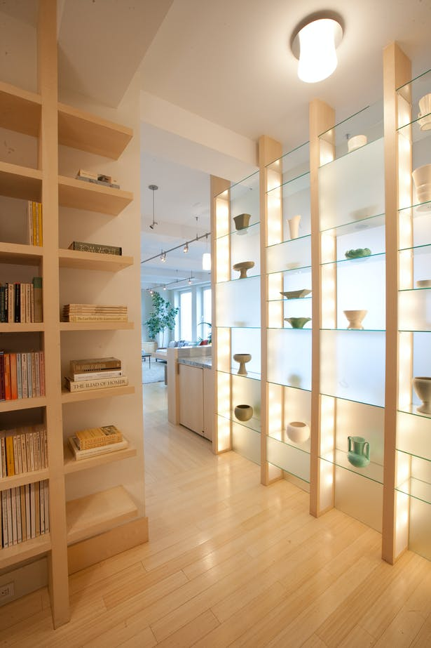 These illuminated, etched glass shelves create a bright welcome while screening the kitchen from the foyer.