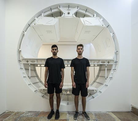 Charles Weinberg and Shai Ben-Ami standing in front of their 1:1 scale model. Image © Michael Shvadron via Charles Weinberg and Shai Ben-Ami