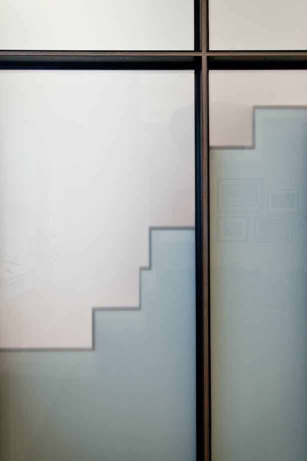 Translucent Wall Panels Allow Daylight and Project a Profile of the Quirky Alternating Tread Stair