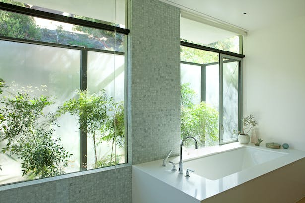 The tub sits sits in the 'wet zone' of marble, next to the garden. Open the window and you're sitting almost outside!