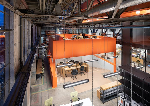 A lowered working pit, where oil was once collected, has been transformed into an orange furniture element. This element includes a mezzanine level with places for concentrated work and a view to the outside.