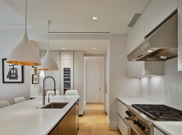 The kitchen features very clean and minimal cabinetry design fabricated by Cesar Kitchens.