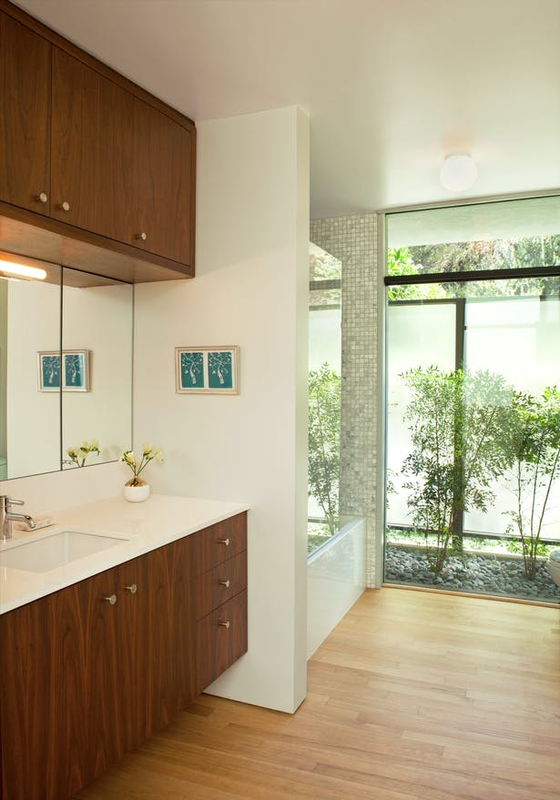 The children's bathroom with it's full-height window to the garden. The shower/tub is defined by mosaic marble walls, and the vanity is a floating walnut cabinet with a white Caesarstone top.