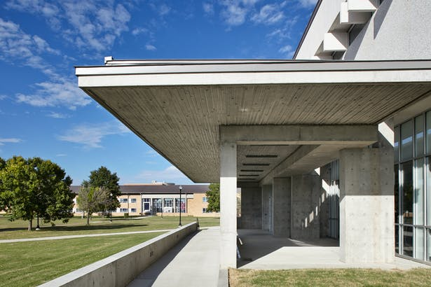 New cast-in-place concrete porch at main entrance becomes the campus