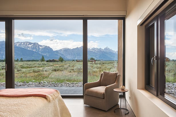 A Lift & Slide Door from Zola Windows opens directly from the master bedroom onto the sage brush landscape that surrounds the home.