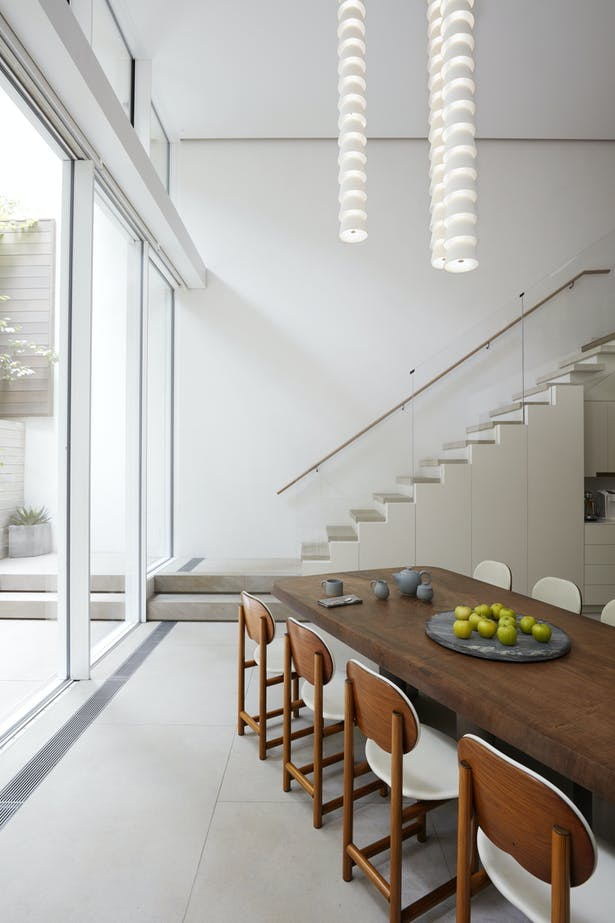 The open kitchen and dining area are on the garden level. Ample storage was accommodated under the steps of the staircase leading to the upper floors.