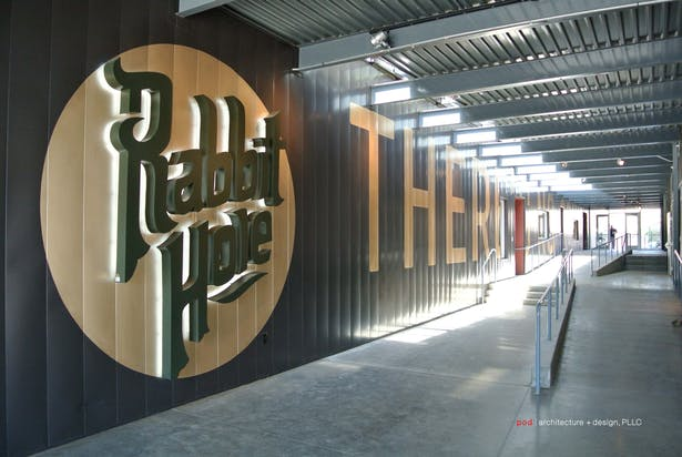 Custom-designed signage, also created by pod architecture + design, welcomes visitors to Rabbit Hole.