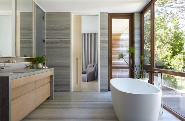 Ocean blue travertine and bleached walnut master bathroom w/ signature KOS+A bathtub. Joshua McHugh Photography