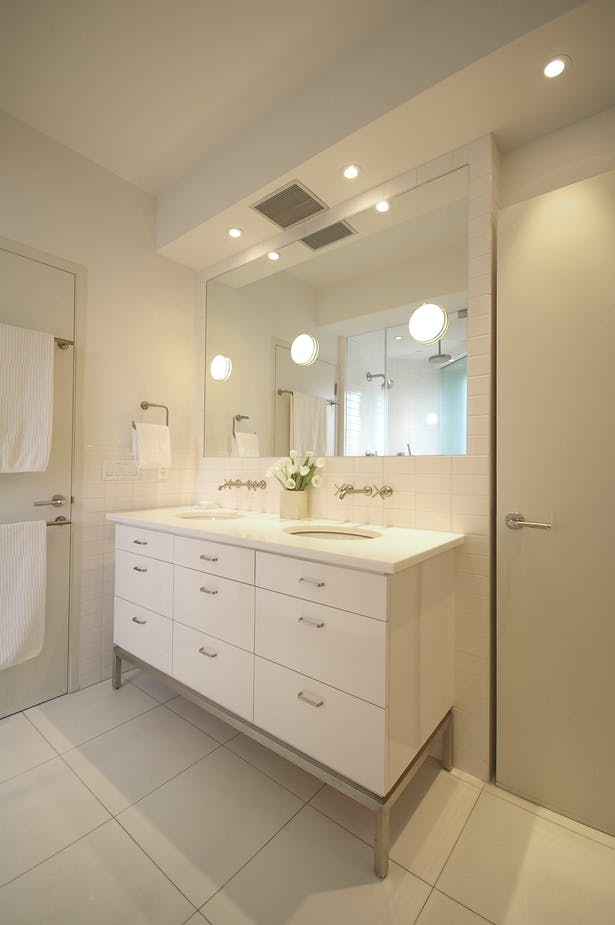 The large double vanity features wall-mounted fittings and a large mirror set flush with the surrounding tile border; large 'can' lights were recessed into the wet wall beyond the mirror to provide brilliant illumination while keeping the perimeter of the room crisp and taught. The vanity cabinet features custom stainless steel legs reminiscent of details used elsewhere in the apartment.