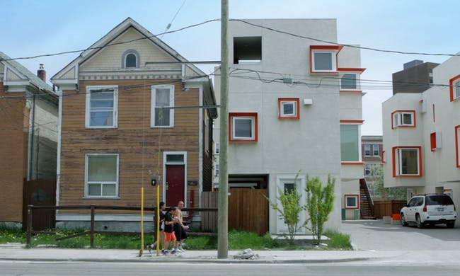Surreal quality ... Centre Village, right, with Winnipeg's more typical wood-framed gabled houses, left - Photograph In Contex