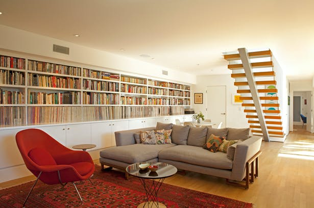 The lower floor has been turned into a den, where formerly it had been more divided up. A long bookcase of vinyl records and books frames the room.