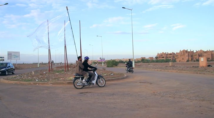 In 'Place of Dead Roads,' the two riders aimlessly loop around an unfinished racetrack, an abandoned project by the Moroccan government. The transparent flag seems to take on the architecture it covers, implicitly demanding an enframent that simultaneously escapes grasp. Credit: Melia/Bitelli