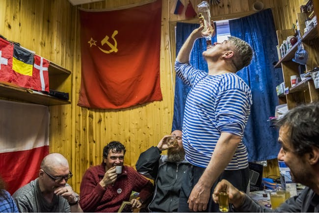 Russians and a Chilean scientist drink homemade Vodka (photo by Daniel Berehulak for the New York Times)