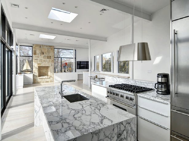 Stunning white marble countertops and modern fixtures give the open concept kitchen a clean, crisp finish.