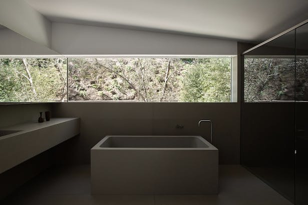 'A custom concrete tub and vanity in the master bathroom was inspired by one of the client's favorite architects, John Pawson, who designed something similar in his Baron House. A room-width window illuminates the space, enhanced by mirrors on both sides.'