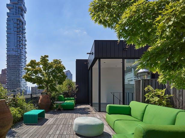 Wood flooring and abundant plantings provide a rooftop sanctuary.