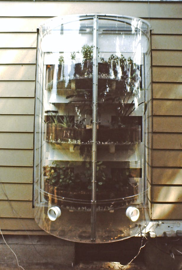 The Solar Round, 1980. A small greenhouse module hung onto a house with built-in solar thermal mass and plant shelves. during the day the plants are on the outside of the house contained within the plastic cylinder. At night the plants and solar thermal mass rotate to the inside.