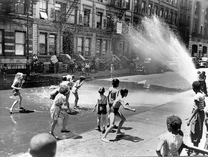 New York, New York. Children escape the heat of the East Side by using fire hydrant as a shower bath in 1943. Photography by Roger Smith. Image courtesy of Library of Congress