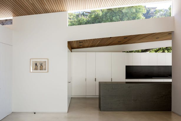 'Clerestory windows mark overhanging sections of the roof while emphasizing its butterfly shape. The dining area flows into a new kitchen, which features new lacquered cabinetry and an inset area for the cooktop. A door to the left provides access to the carport.'