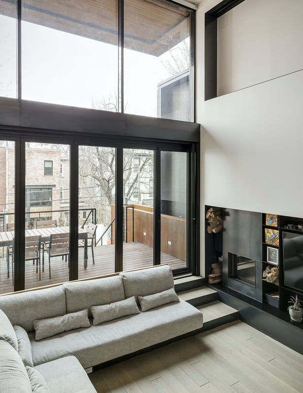 Wall of Folding Glass Doors Opens Living Space to Dining Terrace and Backyard