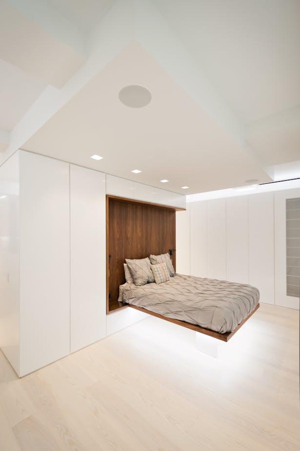 A Custom Built-In Walnut Bed Looks Like It's Floating with Linear Lighting Below