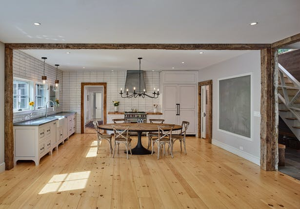 The wide-planked pine floors of the original house were extended into this addition, which found its form in a large open-plan kitchen and living room.
