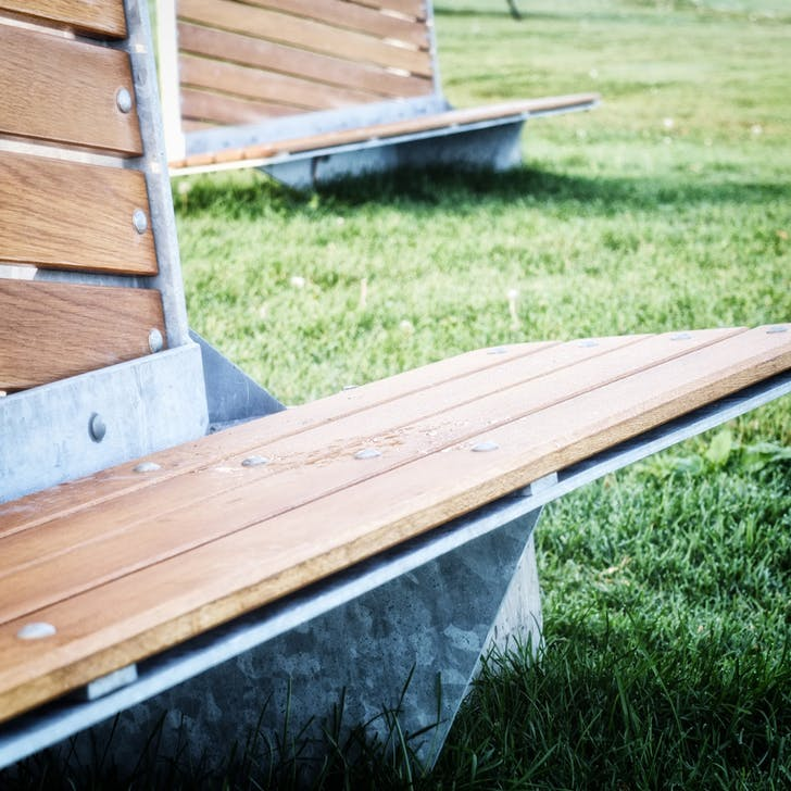 The bench design combines white oak planks with concrete and metal.