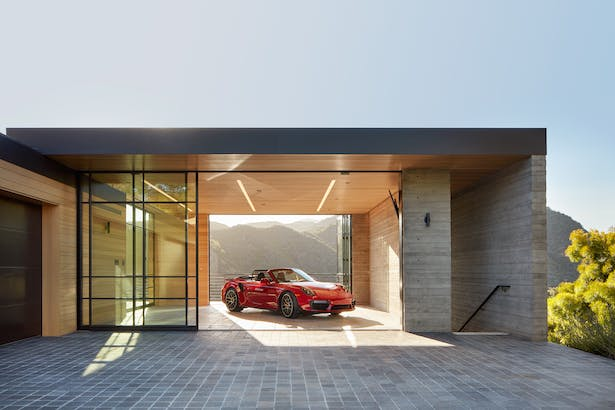 Minimal in form, the layered design respects the home's surroundings, catering to the entrepreneurial homeowners' need as both a full-time residence and part-time wellness retreat. The show garage, shown here, doubles as an open-air yoga studio. (Roger Davies Photography)
