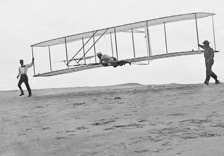 Photo of the Wright brothers' third test glider being launched at Kill Devil Hills, North Carolina, on October 10, 1902. Wilbur Wright is at the controls, Orville Wright is at left, and Dan Tate (a local resident and friend of the Wright brothers) is at right