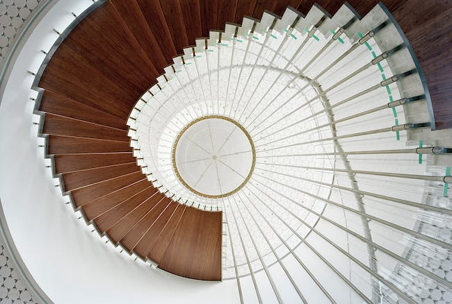 The suspended spiral stair as seen from below. The steps are made of solid bamboo material, and the entire structure is suspended from the ceiling with stainless steel rods. (Photo: Jussi Tiainen)