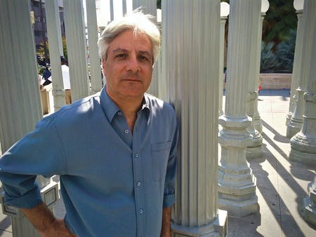 Author David Ulin standing in Chris Burden's 'Urban Light' installation, in front of the Los Angeles County Museum of Art (photo via VQRonline).