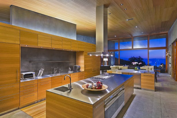 The secondary material of wood brings warmth through the ceiling and built-ins found in the kitchen.