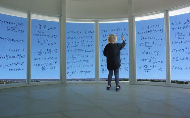 Detail view of a researcher writing equations on the curved glass panels.