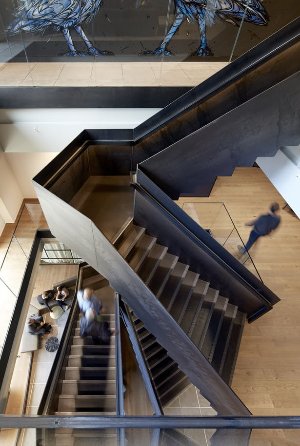 The patinated steel staircase drives interactions between staff and visitors