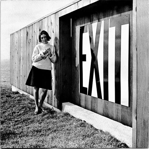 Barbara Stauffacher Solomon beside an enamel exit sign at Lawrence Halprin's house at The Sea Ranch