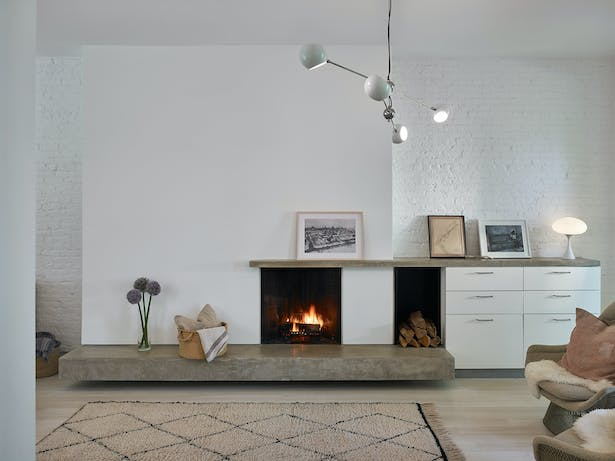 The fireplace with concrete slab front adds a subtle contrast to the white oak floors.