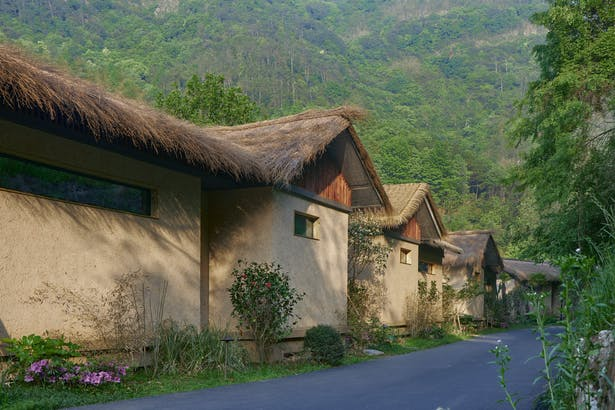 imitated rammed earth thatched cottage