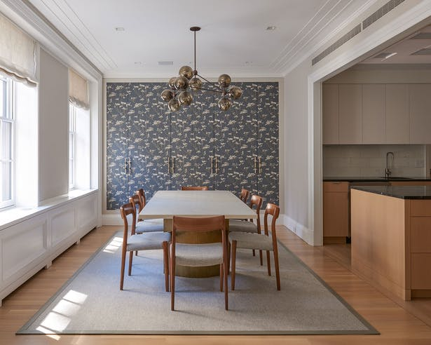 Dining room with custom wallpaper that conceals additional storage.