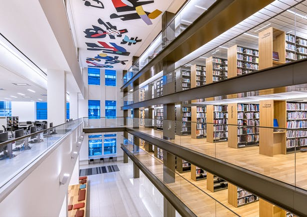 Through the library's 40th Street windows, passers-by will see the northern end of the book stacks, visible as a continuous vertical wall of book spines welcoming New Yorkers into the space to browse. Image copyright by Max Touhey