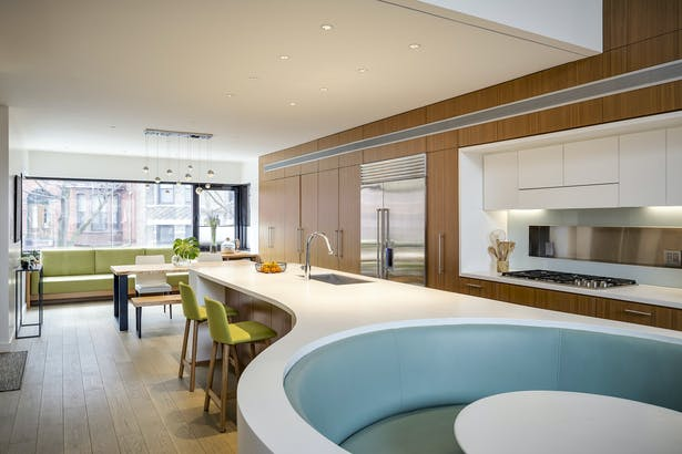 Curving Corian Island Anchors Double Height Living Space
