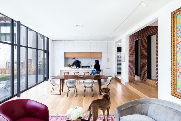 In the transitional space (seen to the right), the red brick rear wall of the old house stands in dramatic contrast to the addition's smooth white walls. Its presence pays homage to the architectural heritage of the original Georgian Revival house.